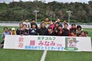 教室に参加した子どもたちと笑顔で記念撮影する勝選手と父の秀樹さん(前列中央)=24日、与論町多目的運動広場
