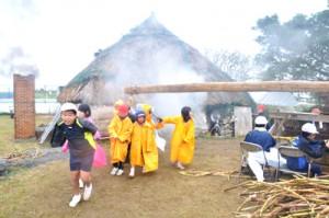 雨の中、サタグルマを回してキビを搾る児童ら=5日、和泊町の大城小