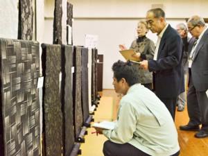 計86点の出品があった紬グランプリと翔けあまみの審査=20日、奄美市名瀬浦上町の奄美市産業支援センター