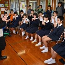 大城支部長(左)からオカリナの演奏方法を学ぶ児童生徒たち=26日、崎原小中学校