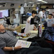県赤十字センターのバス内で献血に協力する住民ら=19日、瀬戸内町