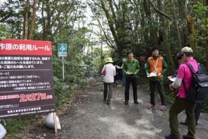 利用規制の試行が始まり、観光客にチラシを配布する関係機関の職員ら=27日、奄美市名瀬