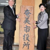 閉庁式で看板を取り外す朝山市長(左)と師玉議長=15日、奄美市役所旧庁舎