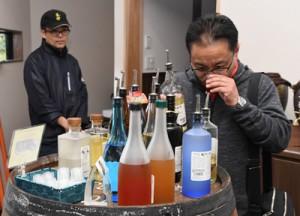 黒糖焼酎を試飲する鎌田さん(右)=1日、龍郷町の町田酒造