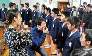 相手に思いを伝えることを意識しながら、一緒に歌を歌う劇団四季の俳優と児童ら=8日、知名町の下平川小学校