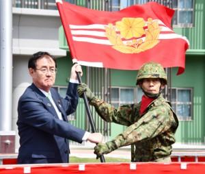 原田副大臣から隊旗を受け取る平田奄美警備隊長(右)=31日、奄美市名瀬大熊