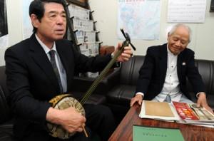 三線「直富主の真壁」の音色を披露する森英也さん(左)と島岡稔さん=29日、大島支庁記者クラブ