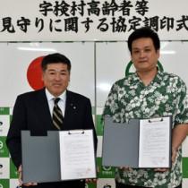 高齢者の見守りへ協定書を交わした元山村長(左)と里本部長=15日、宇検村役場