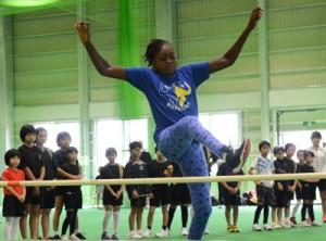 子どもたちの前で跳躍するカリファ選手=2日、徳之島町