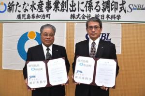 人工シラスウナギの大量生産実現に向けて協定を結んだ新日本科学の永田社長(右)と和泊町の伊地知町長=20日、同町役場
