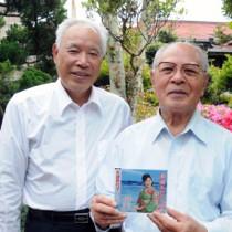 「南国エレジー」のリメイク盤CDを手にする竿田富夫さん(右)と山下幸秀さん=30日、和泊町