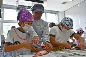岩橋会長(中央)のアドバイスを受けながら魚をさばく児童たち=22日、瀬戸内町の加計呂麻島展示・体験交流館
