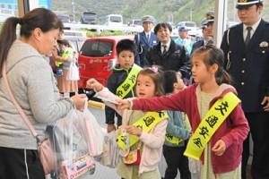 買い物客に交通安全を呼び掛け、チラシを手渡す奄美署員の子どもたち=9日、奄美市名瀬
