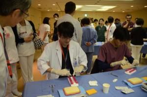 筋膜を想定した2本のチューブを手術で使われる糸で結び付ける研修医たち=13日、奄美市名瀬