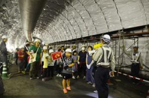 建設中の宮古崎トンネル内部を見学する親子=3日、大和村国直