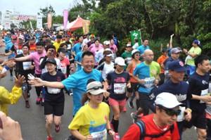 スタートで一斉に走り出すフルマラソンの走者=10日、与論町茶花