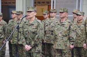 大熊公民館での陸上自衛隊歓迎セレモニーであいさつをする平田浩二1等陸佐(中央)=15日、奄美市名瀬