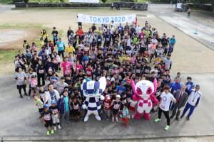 東京2020マスコットや元サッカー日本代表の平瀬さんらと記念撮影する俊寛ジョギング大会出場者=3日、喜界町