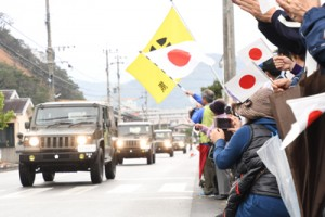 奄美大島に到着し、市民に迎えられながら奄美市内を通過する自衛隊車両=15日、奄美市名瀬大熊町