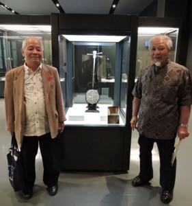 (左から)「直富主の真壁」の前で出会いを喜ぶ島岡さんと沖縄奄美連合会の奥田末吉会長=4日、沖縄県立博物館・美術館