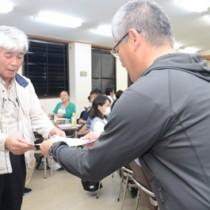 エコツアーガイド育成研修の最終回で、修了証を受け取る受講生=6日、奄美市名瀬の奄美会館