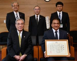 朝山毅奄美市長(前列左)から感謝状を授与された對喜社長(前列右)=12日、奄美市役所