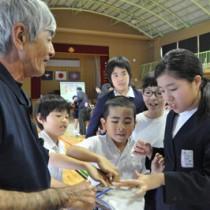 リュウキュウアユに触れて雄と雌の違いを学ぶ児童たち=28日、龍郷町の戸口小学校