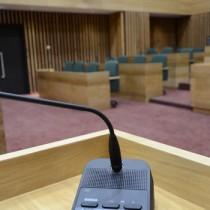 電子表決を行う投票機。賛否のボタンを押すと奥のモニターに結果が表示される。左から「賛成」「反対」=20日、奄美市議会議場