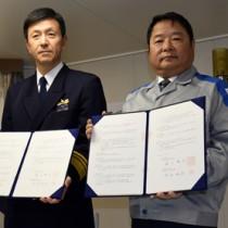 災害時の連携協定を結んだ第10管区海上保安本部の遠山本部長(左)と、九州電力の池辺社長=6日、鹿児島市の巡視船さつま内