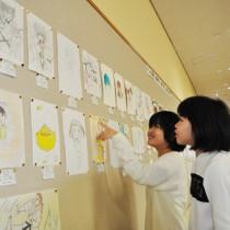 75点の力作が並ぶ合同作品展=23日、県立奄美図書館