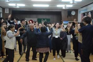 八月踊りで交流するツアー参加者と集落住民=20日、宇検村芦検公民館
