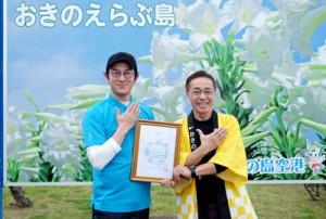 おきのえらぶ島観光親善大使の委嘱を受けた俳優の田上晃吉さん(左)と、同観光協会の前会長(提供写真)=18日、和泊町