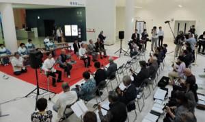 時報に合わせ一斉に「かぎやで風」を演奏する参加者ら=4日、沖縄県立博物館・美術館
