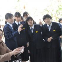 友人たちと掲示板の番号を確認し合う受験生ら=14日、奄美市名瀬の県立大島高校