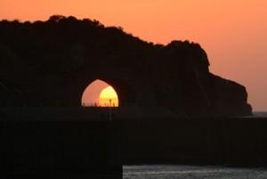 かがんばなトンネル越しに沈んでいく夕日=13日午後6時23分、龍郷町円