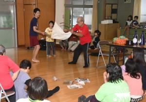 子どもたちにハブの捕り方を教える中原さん(中央)=29日、奄美市名瀬の春日町集会所