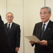 男子生徒の父親に回答書を渡す朝山市長(右)=2日、奄美市役所