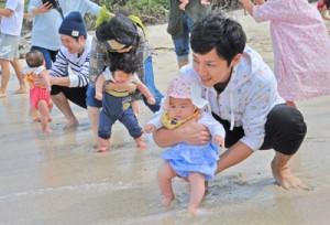 無病息災を祈って子の足を海水に浸す家族ら=7日、奄美市名瀬の大浜海浜公園