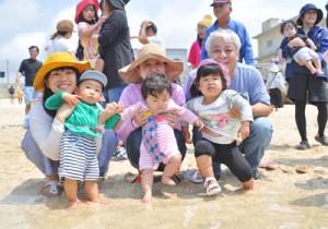 赤ちゃんの足を海水に浸して健やかな成長を願うイベント参加者=7日、知名町屋子母