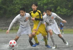 【2次予選】雨の中、ボールを競り合う小宿とT・S・C奄美U―15の選手ら=29日、旧大島工業高校グラウンド
