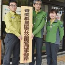 新しい看板を掲げる職員ら=1日、大和村の奄美群島国立公園管理事務所