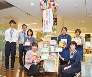 開館10周年を手づくりのくす玉で祝う奄美図書館の職員ら=23日、奄美市名瀬