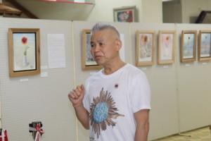 喜界島の特攻花絵画展開催の思いを語る横山さん=25日、町中央公民館