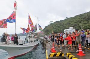 漁船から振る舞われる祝い餅に手を伸ばす参加者ら= 28日、瀬戸内町加計呂麻島芝