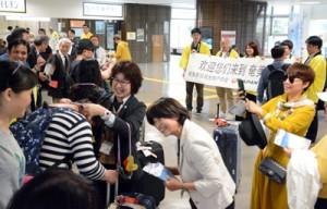 横断幕と黒糖レイでツアー一行を出迎えた歓迎セレモニー=9日、奄美空港