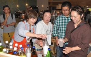 来場者にハイサワーの試飲を勧める田中社長(左から2人目)=6日、和泊町のおきえらぶ百貨店
