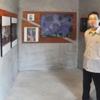 本土と沖永良部島を行き来しながら生活する写真家の園耕治郎さん=11日、知名町やこもハウス2階の作品展示室
