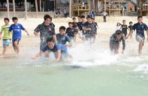 駆け足で海に入る小中学生ら=7日、奄美市笠利町の用安海岸