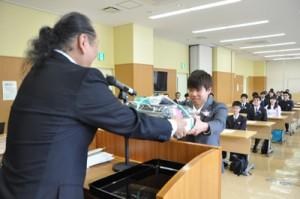 福山校長からノートパソコンを貸与される新入生=12日、奄美市名瀬