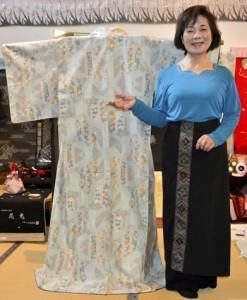 宮崎さんが着用したものと同じ柄の着物の横で笑顔を見せる前田さん=3日、奄美市笠利町のまえだ屋
